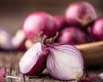 Onion. Red onions on very old oak wood board. Selective focus.